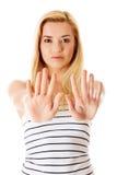 Mujer joven que hace la muestra de la parada en el fondo blanco Fotografía de archivo libre de regalías