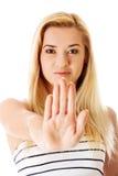Mujer joven que hace la muestra de la parada en el fondo blanco Foto de archivo libre de regalías