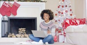 Mujer joven que hace la Navidad que hace compras en línea Imágenes de archivo libres de regalías