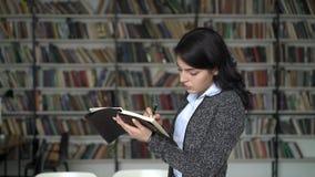 Mujer joven que hace la nota en un blocknote en el fondo de los estantes de la biblioteca almacen de metraje de vídeo