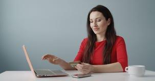 Mujer joven que hace la tarjeta de crédito que se sostiene que hace compras en línea delante de reaccionar del cuaderno feliz par almacen de metraje de vídeo