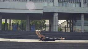 Mujer joven que hace la yoga - surya namascar