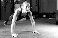 Mujer joven que hace las flexiones de brazos - entrenamiento del crossfit Imagenes de archivo