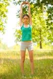 Mujer joven que hace los aeróbicos al aire libre Foto de archivo