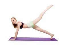 Mujer joven que hace los ejercicios del deporte aislados foto de archivo libre de regalías