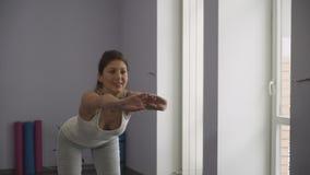 Mujer joven que hace los ejercicios para la parte posterior almacen de video
