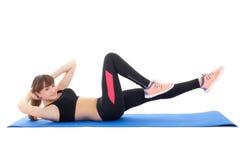 Mujer joven que hace los ejercicios para los músculos abdominales aislados en wh Imagen de archivo libre de regalías