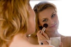 Mujer joven que hace maquillaje Imagen de archivo libre de regalías