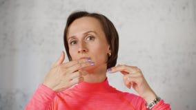 Mujer joven que hace masaje de cara y que rejuvenece la cámara delantera de los ejercicios Mujer de Porrtait que hace ejercicios  metrajes