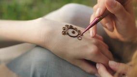 Mujer joven que hace mehendi floral en una mano usando la alheña almacen de video