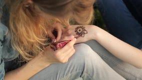 Mujer joven que hace mehendi floral en una mano usando la alheña almacen de metraje de vídeo