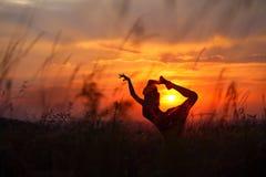Mujer joven que hace movimiento flexible de la danza durante puesta del sol Imagen de archivo libre de regalías