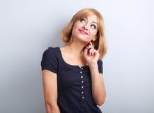 Mujer joven que hace muecas de pensamiento divertida hermosa que mira para arriba en azul Foto de archivo
