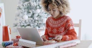 Mujer joven que hace Navidad que hace compras en línea Fotos de archivo libres de regalías