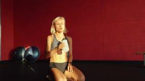 Mujer joven que hace pectorales Hembra muscular que hace flexiones de brazos en la estera del ejercicio almacen de video