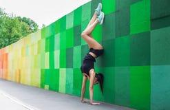 Mujer joven que hace posición del pino en la calle de la ciudad Fotos de archivo