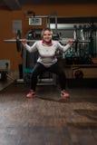 Mujer joven que hace posición en cuclillas del Barbell del ejercicio Fotos de archivo