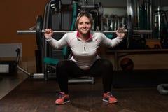 Mujer joven que hace posición en cuclillas del Barbell del ejercicio Imagen de archivo
