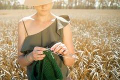 Mujer joven que hace punto en el campo de trigo imagenes de archivo