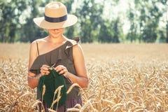 Mujer joven que hace punto en el campo de trigo Imágenes de archivo libres de regalías