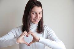 Mujer joven que hace símbolo del corazón con las manos Fotografía de archivo