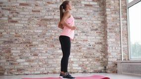 Mujer joven que hace sentar-UPS activo para consolidar los pies en el centro de deportes almacen de metraje de vídeo