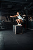 Mujer joven que hace un ejercicio del salto de la caja Foto de archivo