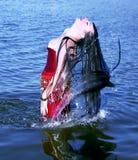 Mujer joven que hace un pelo largo del chapoteo del agua en el mar Fotografía de archivo