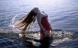 Mujer joven que hace un pelo largo del chapoteo del agua en el mar Fotos de archivo libres de regalías