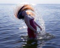 Mujer joven que hace un pelo largo del chapoteo del agua en el mar Imágenes de archivo libres de regalías