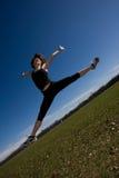 Mujer joven que hace un salto Imagen de archivo libre de regalías
