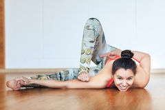 Mujer joven que hace una actitud difícil de la yoga práctica fotografía de archivo libre de regalías