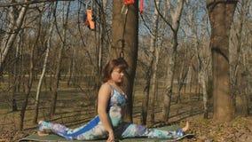 Mujer joven que hace una fractura al aire libre en la alfombra almacen de video