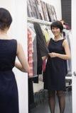 Mujer joven que hace una pausa el estante de la ropa delante del espejo fotos de archivo