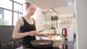 Mujer joven que hace una pausa la estufa en la cocina y que prepara el desayuno para la familia, vídeo de la forma de vida diario almacen de metraje de vídeo