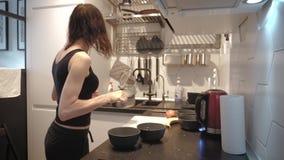 Mujer joven que hace una pausa la estufa en la cocina y que prepara el desayuno para la familia, v?deo de la forma de vida diario almacen de video