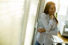 Mujer joven que hace una pausa la ventana Foto de archivo
