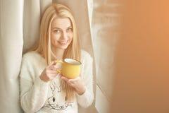 Mujer joven que hace una pausa la ventana con una taza de café, pareciendo exterior y de sonrisa Luz al aire libre natural Foto de archivo