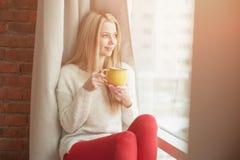 Mujer joven que hace una pausa la ventana con una taza de café, pareciendo exterior y de sonrisa Luz al aire libre natural Foto de archivo libre de regalías