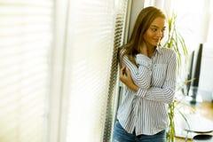 Mujer joven que hace una pausa la ventana en el cuarto Foto de archivo libre de regalías