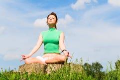 Mujer joven que hace yoga Foto de archivo libre de regalías