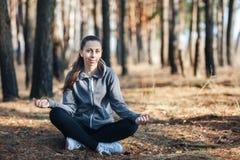 Mujer joven que hace yoga al aire libre en el bosque imagenes de archivo