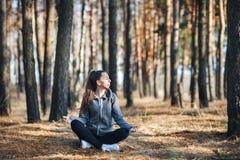 Mujer joven que hace yoga al aire libre en el bosque imágenes de archivo libres de regalías