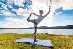 Mujer joven que hace yoga cerca del lago al aire libre, meditación Aptitud del deporte y ejercicio en naturaleza Puesta del sol d Imagenes de archivo