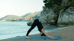 Mujer joven que hace yoga cerca del mar en la puesta del sol en la estera azul al aire libre almacen de metraje de vídeo