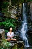 Mujer joven que hace yoga con la flor de loto Fotografía de archivo