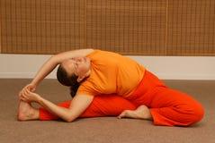 Mujer joven que hace yoga en el cuarto asoleado Imagen de archivo libre de regalías