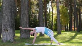 Mujer joven que hace yoga en el parque en el aire abierto Forma de vida sana almacen de video