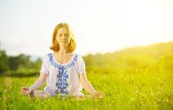 Mujer joven que hace yoga en hierba verde Fotos de archivo libres de regalías