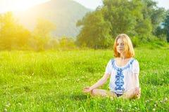 Mujer joven que hace yoga en hierba verde Foto de archivo